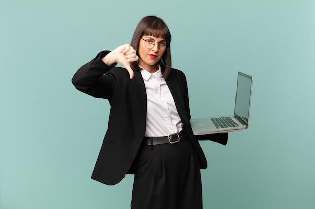 Bizneswoman czuje się zła, zła, zirytowana, rozczarowana lub niezadowolona, pokazując kciuk w dół z poważnym spojrzeniem