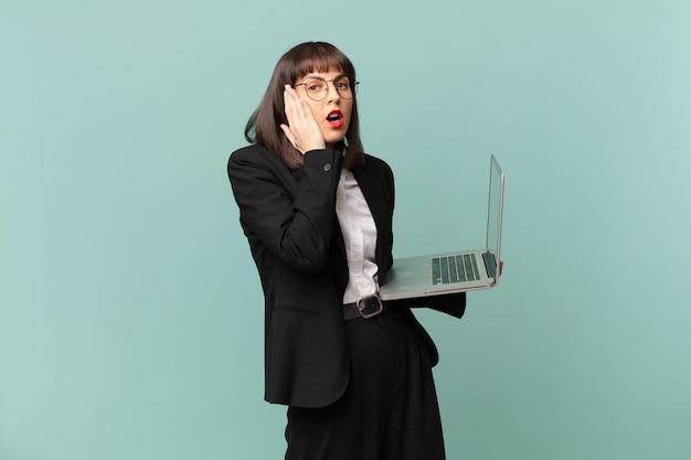 Bizneswoman czuje się zszokowana i przestraszona, wygląda na przerażoną z otwartymi ustami i dłońmi na policzkach