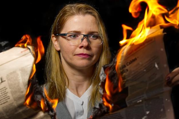 Bizneswoman czyta gorące wiadomości lub czyta wiadomości giełdowe ceny akcji. płonący magazyn w rękach kobiety - koncepcja najświeższych i najświeższych wiadomości