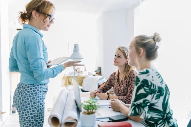 Bizneswoman daje instrukci jej żeński kolega obsiadanie przy miejscem pracy