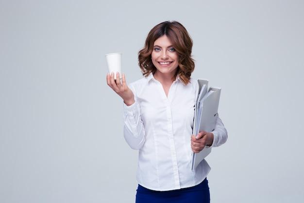 Bizneswoman gospodarstwa foldery i filiżankę z kawą