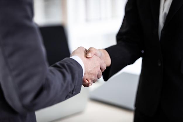 Bizneswoman i biznesmen ściskając ręce w tle pokoju biurowego po podpisaniu umowy lub uścisku dłoni, biznes wyraził zaufanie ośmiela i udaną koncepcję
