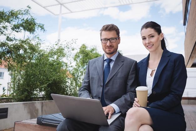 Bizneswoman i kolega za pomocą laptopa