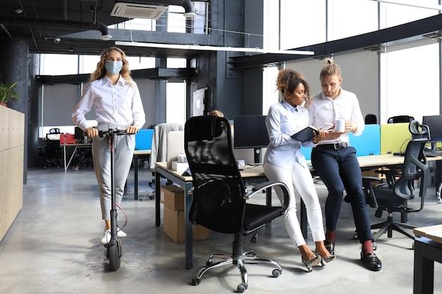 Bizneswoman jazda skuterem w profilaktycznej masce medycznej w epidemii w nowoczesnym biurze na otwartej przestrzeni, koledzy w tle. grupa postępowych ludzi biznesu pracujących razem na starcie.