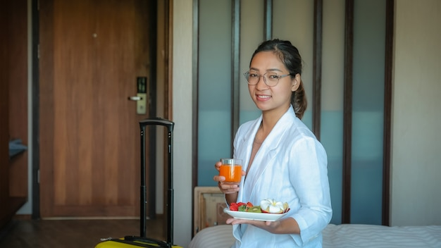 Bizneswoman je owoce i pije sok pomarańczowy na łóżku w luksusowym pokoju hotelowym koncepcja zdrowej żywności