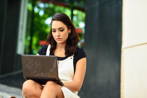 Bizneswoman jest ubranym przypadkowych ubrania pracuje outdoors.