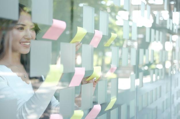 Bizneswoman kobiety myślący planowanie z adhezyjnymi notatkami na szklanej ścianie