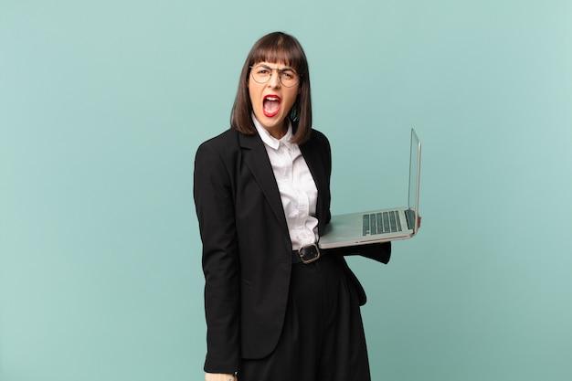 Bizneswoman krzyczy agresywnie, wygląda na bardzo rozgniewaną, sfrustrowaną, wściekłą lub zirytowaną, krzyczy nie