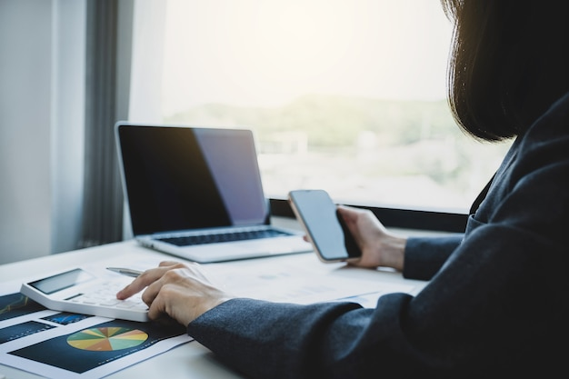 Bizneswoman księgowy ręcznie używa kalkulatora i laptopa robi konto płacąc podatek w biurze roboczym