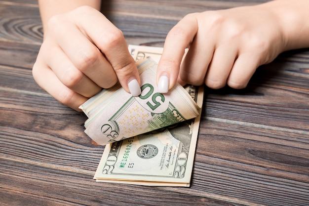 Bizneswoman liczy pięćdziesiąt i dwadzieścia dolarów banknotów