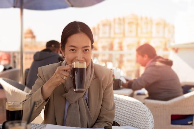 Bizneswoman ma filiżanki kawy plenerową cukiernianą patrzeje kamerę.