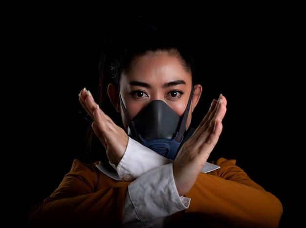 Bizneswoman młoda kobieta asia zakłada maskę n95 respirator w celu ochrony przed chorobami układu oddechowego przenoszonymi drogą powietrzną, kobiety są stop znak ręką