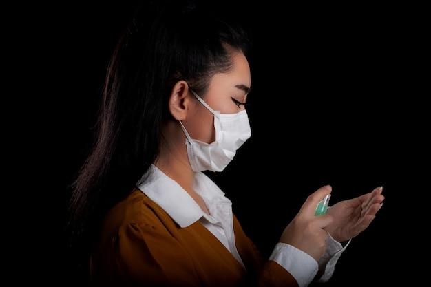 Bizneswoman młodej kobiety z azji zakładającej maskę n95 do respiratora ręką, która nakłada spray alkoholowy z plastikowej butelki lub antybakterii, aby zapobiec rozprzestrzenianiu się zarazków na czarnej powierzchni