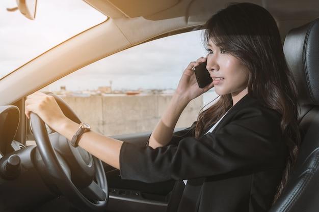 Bizneswoman na telefonie w jej samochodzie.