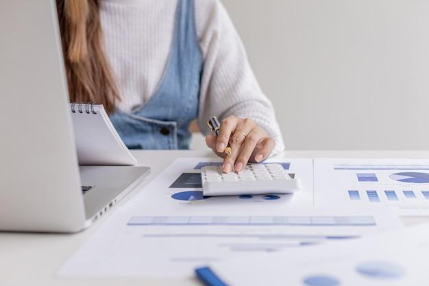 Bizneswoman naciska kalkulator i przegląda dane w zeszycie, sprawdza poprawność danych, zarządza finansami, aby się rozwijać. pojęcie zarządzania finansami.
