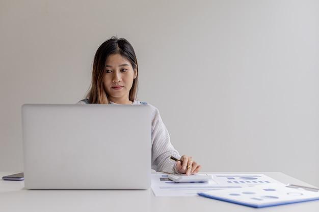 Bizneswoman naciska kalkulator i używa laptopa, rozmawia z menedżerem finansów za pomocą programu do przesyłania wiadomości na laptopie, zarządza finansami, aby się rozwijać. pojęcie zarządzania finansami.