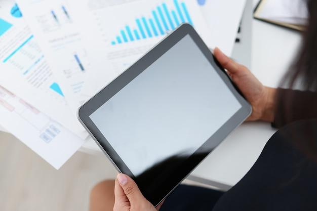 Bizneswoman nauki dokumenty trzymają pastylkę w ona ręki zbliżenie