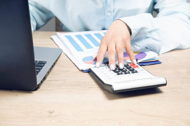 Bizneswoman oblicza za pomocą kalkulatora i studiuje dane w biurze