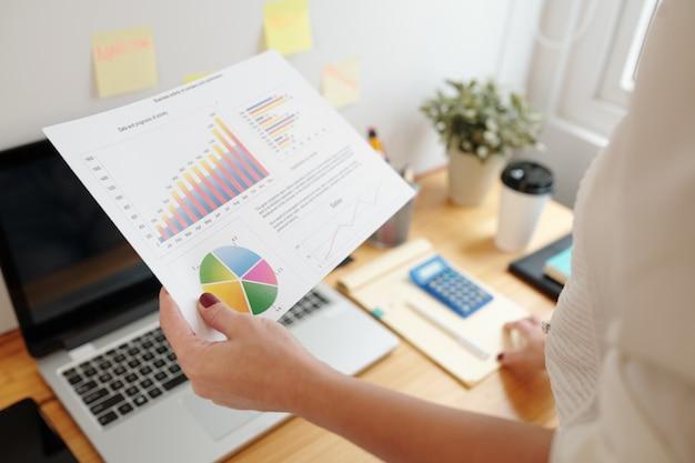 Bizneswoman obrazu z bliska analizujący raport sprzedaży z wykresami i diagramami, aby wyciągnąć wnioski dotyczące rozwoju biznesu
