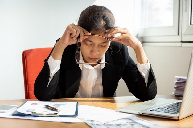 Bizneswoman odpoczywa ręki na głowie z oczami zamkniętymi przy pracy biurkiem w biurze.