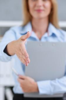 Bizneswoman oferuje rękę, aby wstrząsnąć jak cześć w zbliżeniu biura