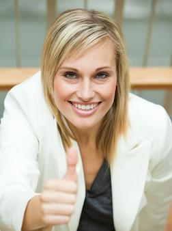 Bizneswoman ono uśmiecha się z jej kciukiem up
