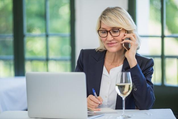 Bizneswoman opowiada na telefonie komórkowym podczas gdy pisać na dzienniczku