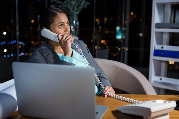 Bizneswoman opowiada na telefonie podczas gdy pracujący w biurze