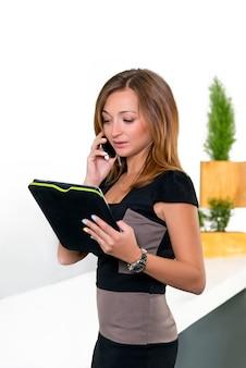 Bizneswoman opowiada na telefonie w biurze i trzyma pastylkę z listą zadania