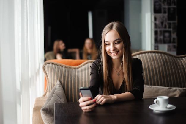 Bizneswoman opowiada na telefonie w sklep z kawą