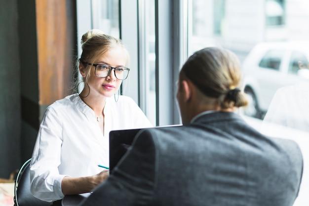 Bizneswoman patrzeje jej kolegi pracuje w caf�
