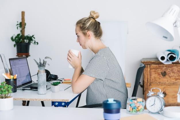 Bizneswoman pije kawę podczas gdy pracujący w biurze