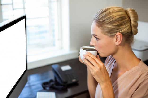 Bizneswoman pije kawę w biurze