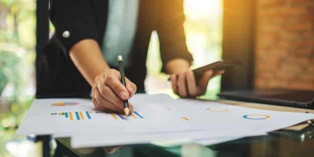 Bizneswoman pisze i pracuje na biznesowych pieniężnych danych i telefonie komórkowym na stole w biurze