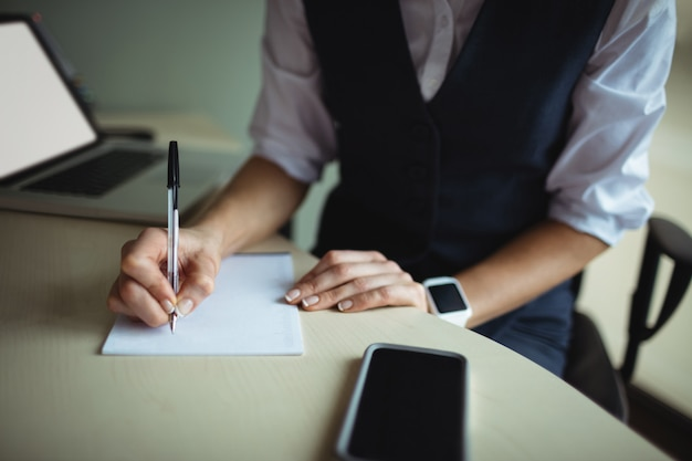 Bizneswoman pisze na notatniku
