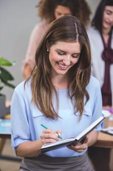 Bizneswoman pisze notatce na dzienniczku