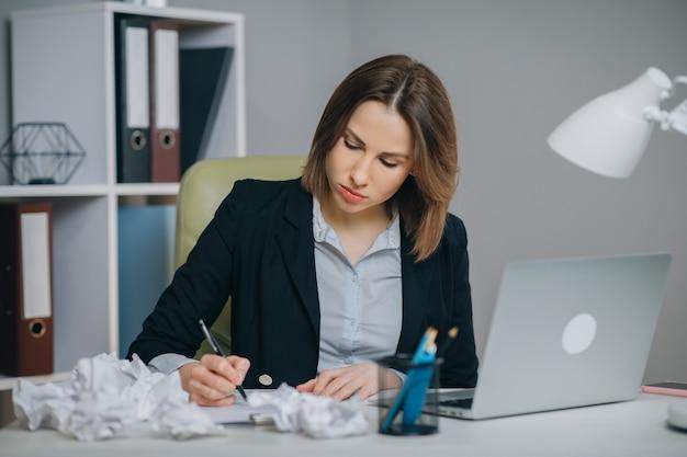 Bizneswoman pisze swoje dzieło, marszczy i marnuje arkusz papieru niezadowolony z rezultatu. zmięte kawałki papieru