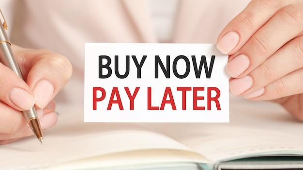 Bizneswoman pisze w zeszycie srebrnym długopisem i trzymaną w ręce karteczką z tekstem: kup teraz, zapłać później