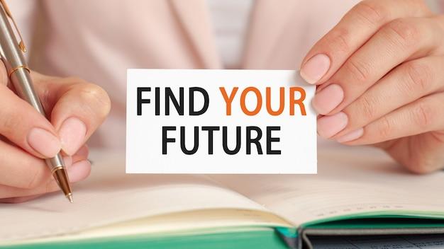 Bizneswoman pisze w zeszycie ze srebrnym długopisem i trzymaną ręką kartę z tekstem znaleźć swoją przyszłość. pomysł na biznes.