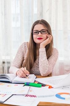 Bizneswoman planuje coś w dzienniku, pracuje w biurze