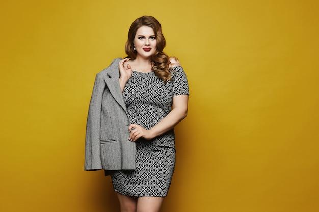 Bizneswoman plus size z jasnym makijażem i stylową fryzurą w sukience z geometrycznymi wzorami pozującymi na żółto, na białym tle