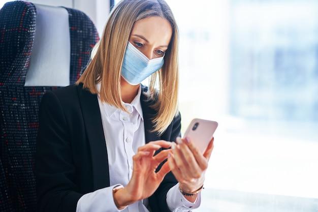 Bizneswoman podjeżdżający do metra w masce w transporcie publicznym za pomocą smartfona