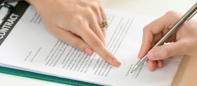 Bizneswoman podpisuje zgodę kontrakt w biurze.