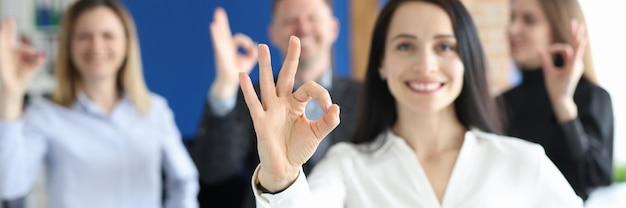 Bizneswoman pokazując ok gest na tle kolegów w biurze zbliżenie