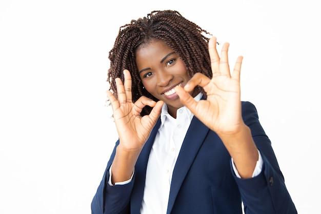 Bizneswoman pokazuje ok szyldowego i ono uśmiecha się przy kamerą
