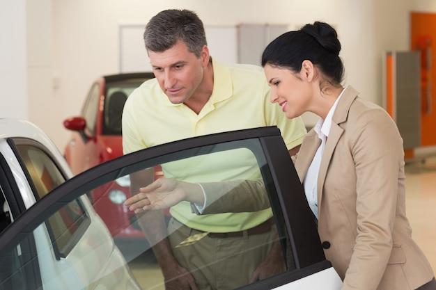 Bizneswoman pokazuje samochodowego wnętrze jej klienci