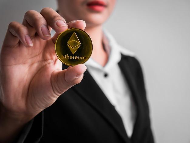 Bizneswoman pokazuje złocistą ethereum monetę.