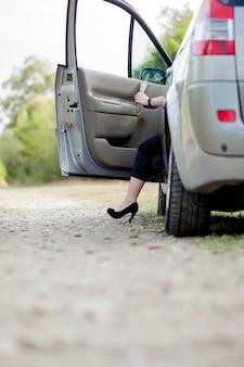 Bizneswoman pozuje blisko białego samochodu i pokazuje jej szczupłe i nikłe nogi blisko jej samochodu. sukces pani w szarej spódnicy pozuje na różowych szpilkach