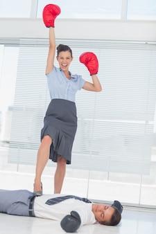 Bizneswoman pozycja na pokonującym biznesmenie jest ubranym bokserskie rękawiczki