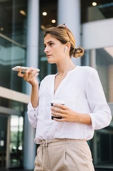Bizneswoman pozycja przed budynkiem biurowym opowiada na głośnikowym telefonie komórkowym